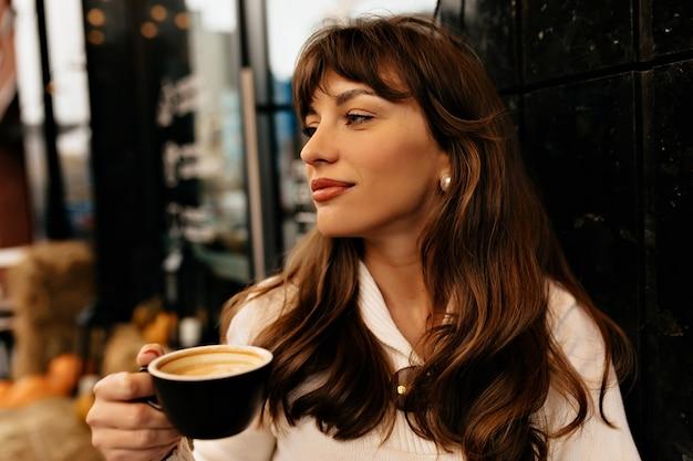 Feche o retrato ao ar livre de uma linda garota encantadora com uma xícara de café descansando em um café ao ar livre no fundo das luzes da cidade. foto de alta qualidade