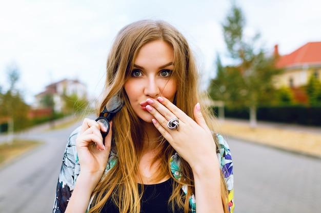 Feche o retrato ao ar livre de uma mulher loira hippie sensual com cabelos longos e maquiagem natural, tempo ventoso e chuvoso, humor triste, coloque as mãos nos lábios, mandando beijo do ar.
