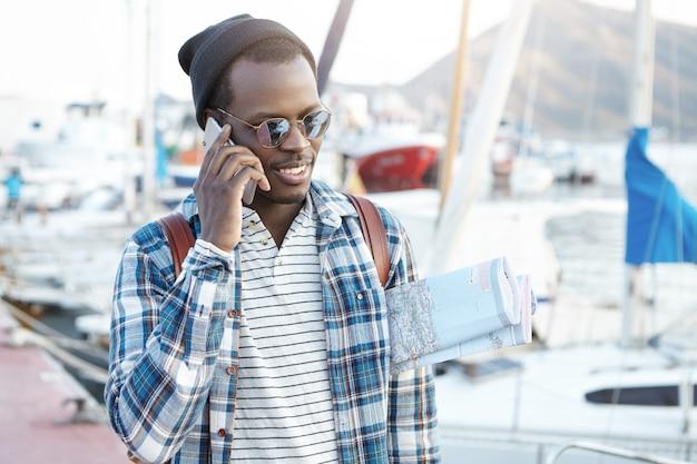 Feche o retrato ao ar livre do carismático jovem afro-americano em roupas elegantes, carregando o mapa de papel debaixo do braço, tendo uma boa conversa por telefone
