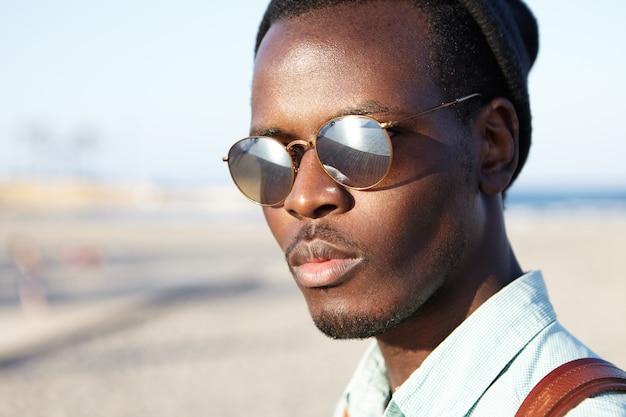 Feche o retrato ao ar livre do jovem afro-americano atraente e confiante em óculos de sol com lentes espelhadas, passando a manhã à beira-mar, decidindo-se, hesitando sobre a escolha da vida difícil