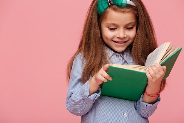 Feche o retrato da adorável menina com cabelos castanhos compridos, lendo um livro interessante, tendo emoções felizes