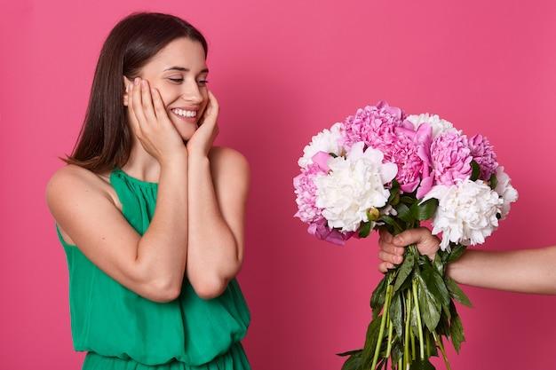 Feche o retrato da adorável mulher morena usa vestido verde posando contra parede rosa, a mão de alguém dá-lhe o buquê de flores peônias, garota mantém as mãos nas bochechas.