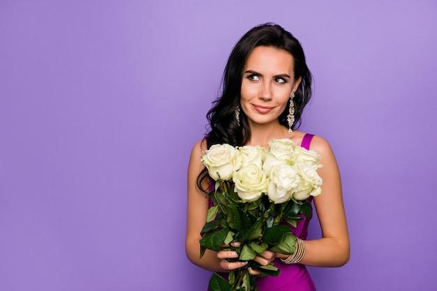 Feche o retrato da adorável senhora segurando rosas isoladas sobre um fundo de cor roxa