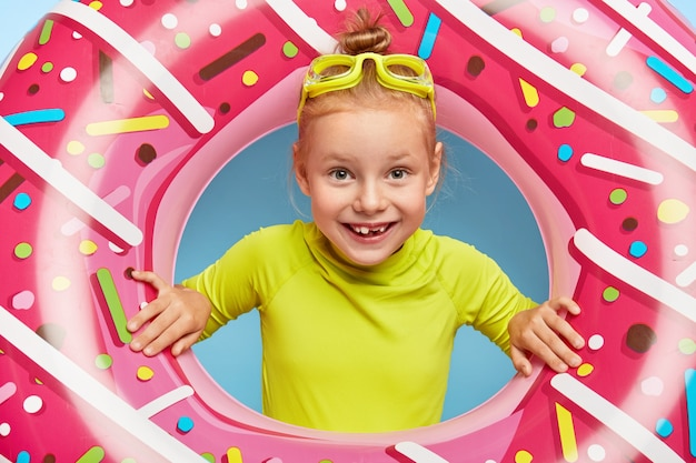 Feche o retrato da alegre adorável menina ruiva enfia a cabeça através do anel de borracha rosa, usa óculos e camiseta brilhante, passa as férias de verão à beira-mar, gosta de nadar. infância feliz e descanso
