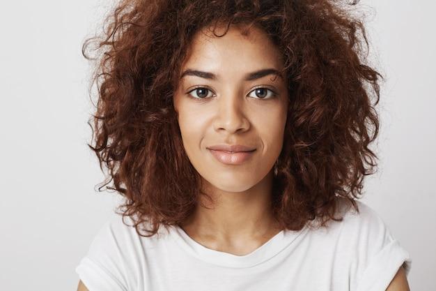 Feche o retrato da bela garota africana com olhos grandes, sorrindo com um sorriso, sentindo-se confiante e calmo, sendo atraente e atraente.