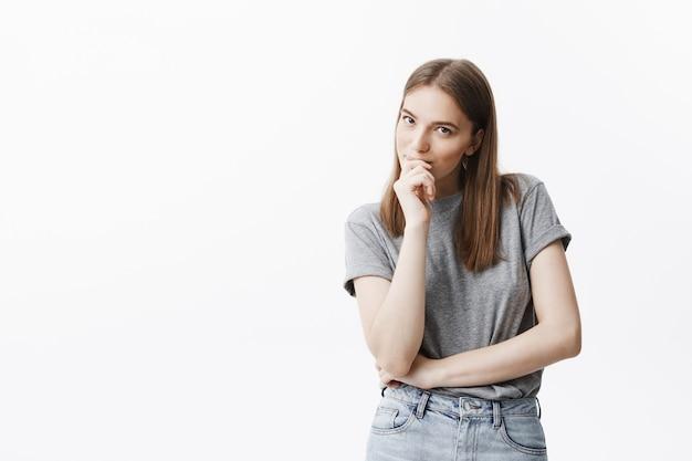 Feche o retrato da bela morena caucasiana jovem com cabelos longos em t-shirt cinza e calça jeans com expressão de rosto pensativo, sorrindo, segurando a mão perto da boca