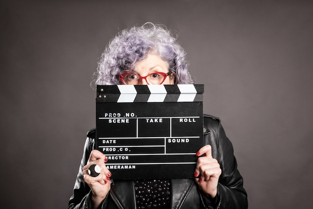 Feche o retrato da bela mulher mais velha segurando um badalo de filme em cinza