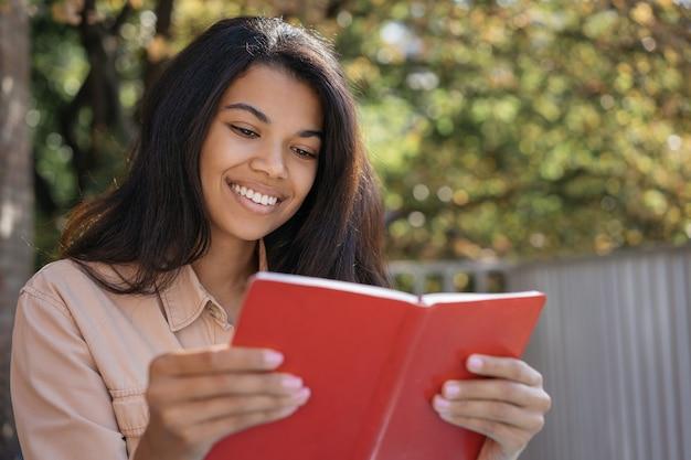 Feche o retrato da bela mulher sorridente, lendo um livro, estudando, aprendendo um idioma, sentado no parque