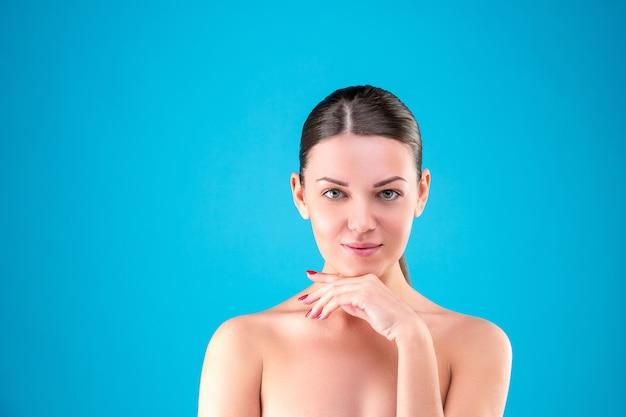 Feche o retrato da beleza da morena jovem sorrindo e tocando seu rosto sobre fundo azul. pele fresca perfeita. conceito de juventude e cuidados com a pele.