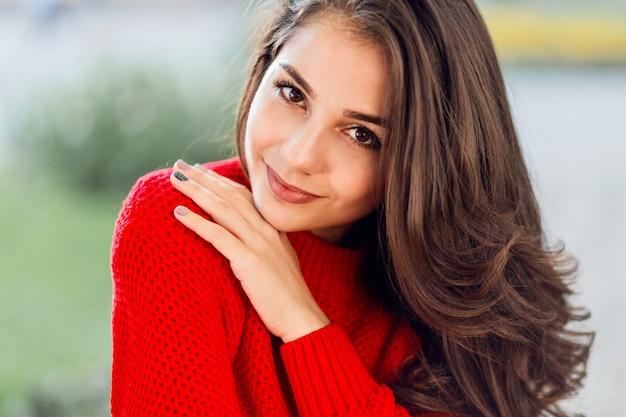 Feche o retrato da beleza da mulher morena com cabelos compridos ondulados, sorriso fofo relaxante no parque outono.