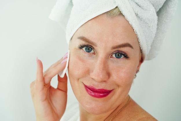 Feche o retrato da beleza de uma jovem atraente e sorridente, limpando o rosto com uma almofada de algodão