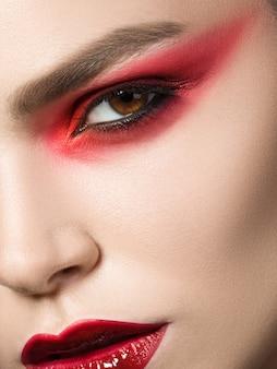 Feche o retrato da beleza de uma jovem com olhos vermelhos esfumados