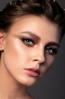 Feche o retrato da beleza de uma jovem com uma bela maquiagem de olhos esfumados bronze