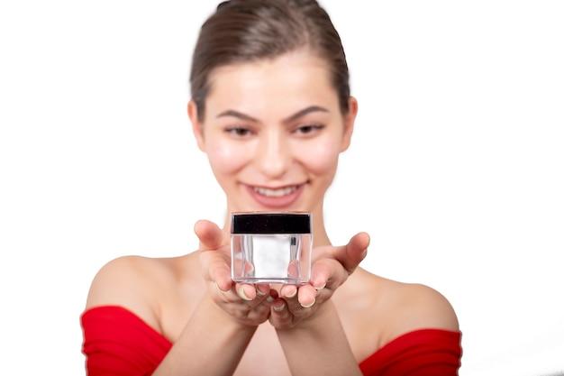 Feche o retrato da beleza de uma linda mulher rindo, aplicando creme facial e olhando isolado