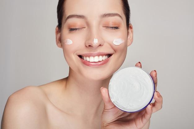 Feche o retrato da beleza de uma mulher bonita meia nua rindo com os olhos fechados detém na mão creme para o rosto.