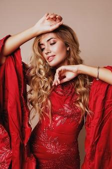 Feche o retrato da beleza de uma mulher loira perfeita com lábios carnudos, maquiagem natural posando em incrível vestido vermelho de luxo com lantejoulas e mangas largas. mãos perto do rosto.