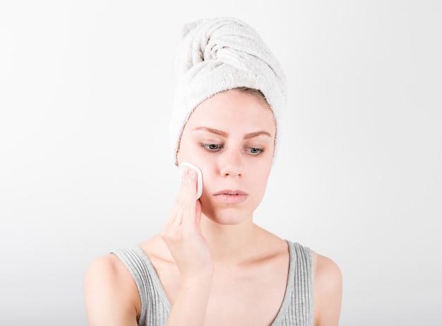 Feche o retrato da beleza de uma mulher sorridente e atraente limpando o rosto com um algodão