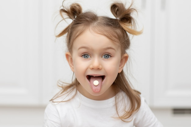 Feche o retrato da criança emocional com pílula ou doce na língua em casa tomando remédio