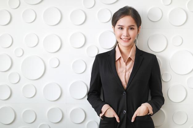 Feche o retrato da empresária asiática em pé, sorria e coloque a mão na bolsa do terno que mostra o conforto de ser fotografado em um fundo que é muito branco de superfície circular.