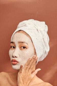 Feche o retrato da encantadora mulher asiática com uma toalha branca na cabeça e uma máscara de argila no rosto.
