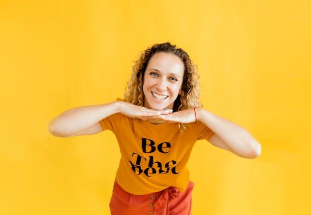Feche o retrato da foto de uma linda garota com cabelos ondulados, segurando as mãos perto de seu queixo, fundo amarelo.