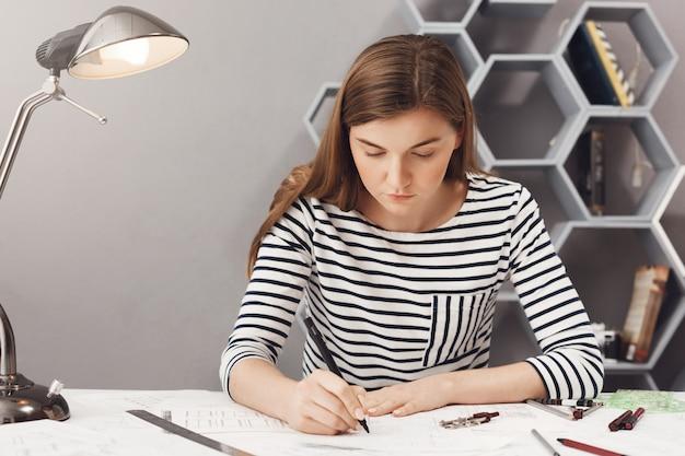 Feche o retrato da garota jovem arquiteto sério fazendo seu trabalho no espaço acolhedor coworking, olhando para o papel com expressão séria e infeliz.