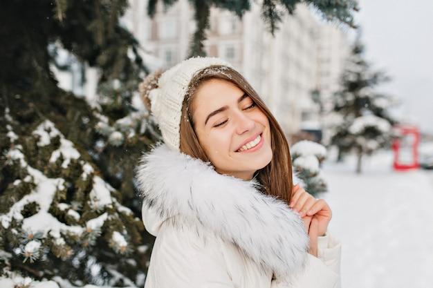 Feche o retrato da incrível mulher alegre em roupas quentes brancas e quentes, aproveitando o inverno na cidade. mulher jovem e bonita na neve, sorrindo com os olhos fechados.
