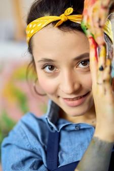 Feche o retrato da jovem artista feminina feliz olhando para a câmera, posando com as mãos