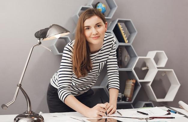 Feche o retrato da jovem encantadora alegre estudante estudante em pé perto da mesa, segurando as mãos em papéis de trabalho com expressão feliz e satisfeita.