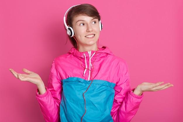 Feche o retrato da jovem morena com fones de ouvido na cabeça, vestida com camisa esporte azul e rosa