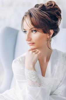Feche o retrato da jovem noiva linda elegante túnica branca, sentado em uma cadeira em um interior brilhante