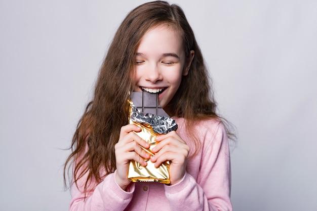 Feche o retrato da linda garota comendo chocolate sobre cinza e sorria
