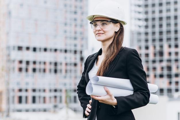 Feche o retrato da linda garota em um capacete de proteção amarelo e óculos de proteção, um conceito arquitetônico