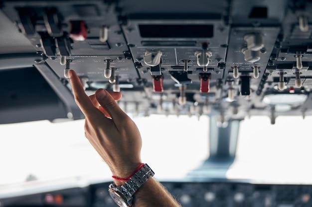 Feche o retrato da mão do homem com o relógio enquanto empurra o painel do moderno avião civil de passageiros