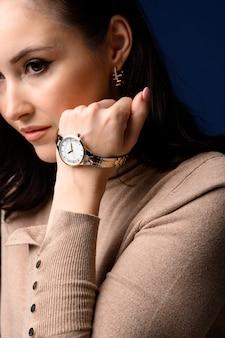 Feche o retrato da meia-idade linda mulher elegante posando. modelo usando relógio de pulso. conceito de moda feminina