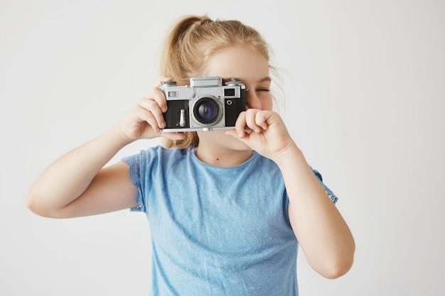 Feche o retrato da menina adorável com cabelos loiros na camiseta azul, indo tirar uma foto de amigos na escola com a câmera de filme.