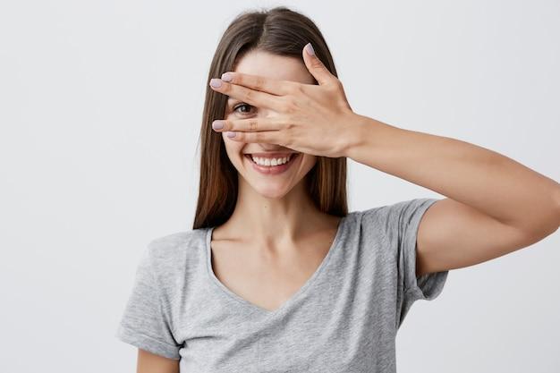 Feche o retrato da menina alegre bonita jovem estudante caucasiano com cabelos longos escuros na camiseta cinza na moda sorrindo com dentes, olhos de roupas com a mão, olhando pelo dedo com um olho.