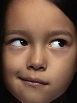 Feche o retrato da menina asiática pequena e emocional.