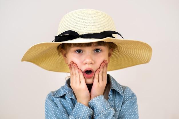 Feche o retrato da menina bonitinha com um chapéu bege com emoção surpresa