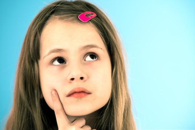 Feche o retrato da menina bonitinha pensativa com grampo de cabelo rosa sobre fundo azul. conceito de sonhos infantis.