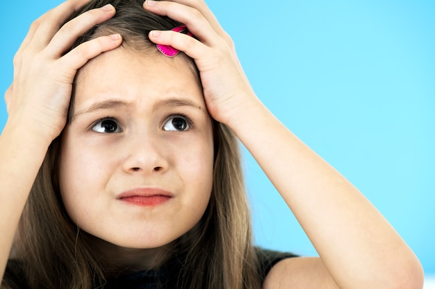 Feche o retrato da menina chateada e pensativa com grampo de cabelo rosa bonito sobre fundo azul.