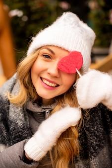 Feche o retrato da menina com pirulito em forma de coração.