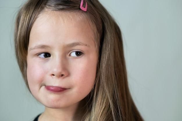 Feche o retrato da menina criança com expressão de rosto engraçado.