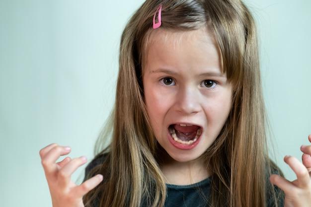 Feche o retrato da menina criança gritando com raiva, olhando agressivamente