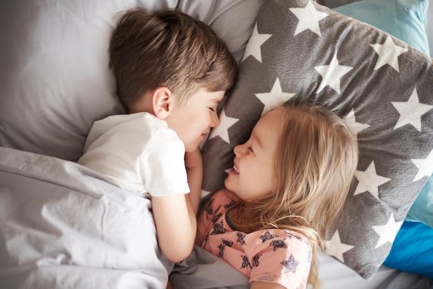 Feche o retrato da menina dormindo ao lado do irmão