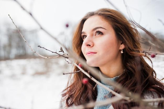 Feche o retrato da menina gentil com casaco cinza perto dos galhos de uma árvore coberta de neve.
