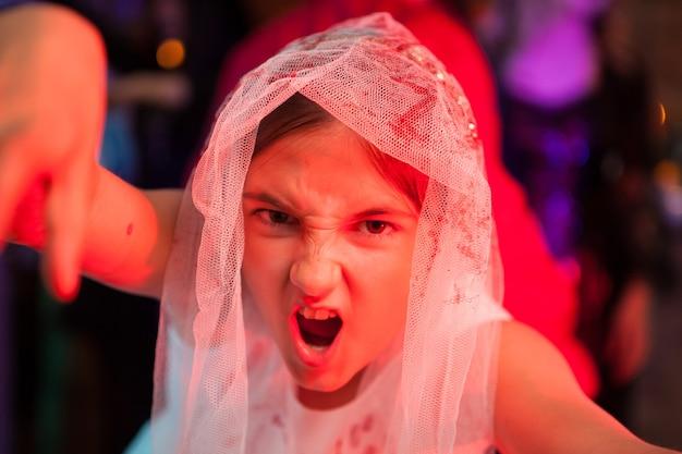 Feche o retrato da menina gritando em uma festa de halloween com vestido de remoção de ervas daninhas. expressão assustadora.