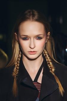 Feche o retrato da menina hippie com tranças no cabelo, olhando severo e vestindo casaco gasto