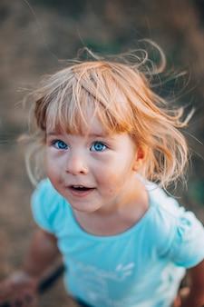 Feche o retrato da menina loira de olhos azuis do lado de fora com cabelos despenteados e rosto sujo surpreso.