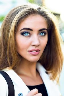 Feche o retrato da moda da mulher elegante, com grandes olhos azuis e lábios maçantes, o estilo da natureza.